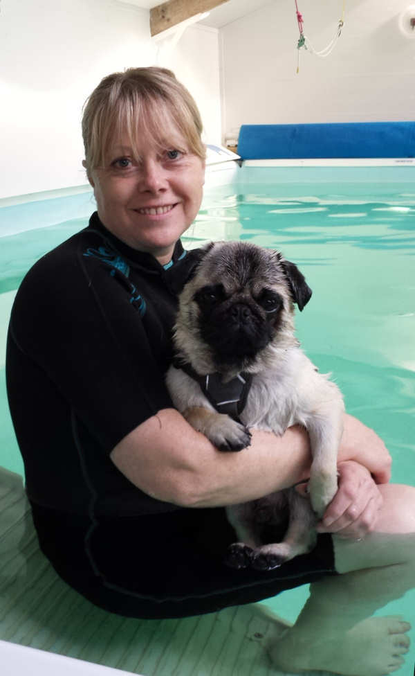 Picture of Jacqui Woodhall holding a pug dog by the hydrotherapy pool